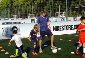 Children practice soccer skills with a sports volunteer at a club in China.