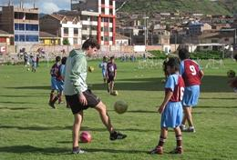 A child practices soccer drills with the help of a volunteer in Peru.