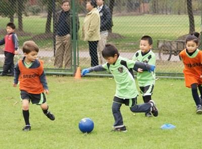 Children play soccer at their school club with a volunteer coach in China