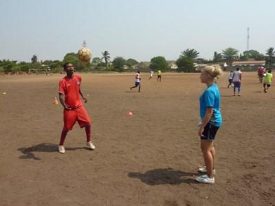 Female volunteer coaches teenagers soccer team in Ghana