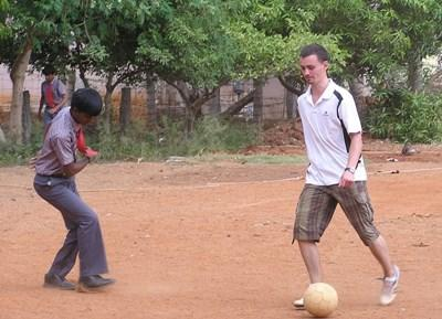 Volunteer plays soccer with a student at a school in India