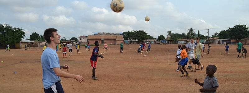 Volunteers coach soccer at a school abroad on the Sports project
