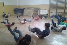 Children stretch with a volunteer sports coach before playing soccer at a school in Romania.