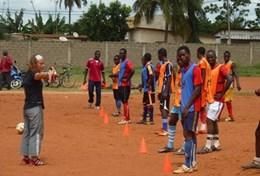 A local team practices soccer drills with a coach volunteering in Togo.