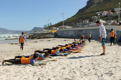 A group of children pay attention to a volunteer during a surfing lesson at Muizenberg beach