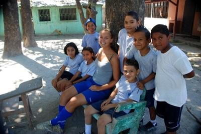 Volunteer soccer coach takes a break with players in a school in Costa Rica, Central America