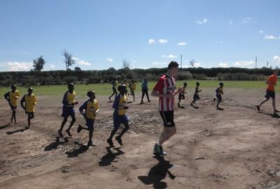 Kenyan school children participate in exercise drills before soccer practice.