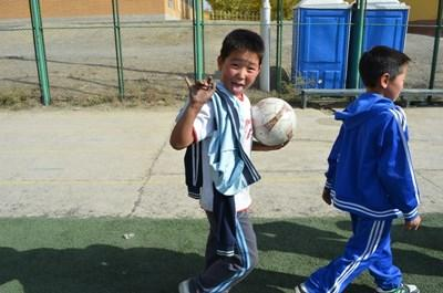 Young boy practices soccer with a volunteer in Mongolia