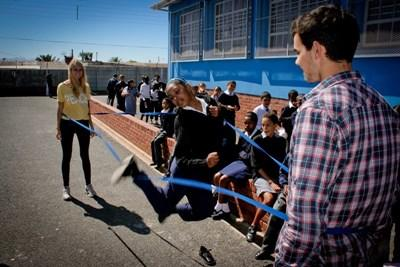 Kids at a school in South Africa jump rope with volunteer coaches