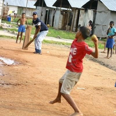 Volunteer coaches play cricket with students in Sri Lank