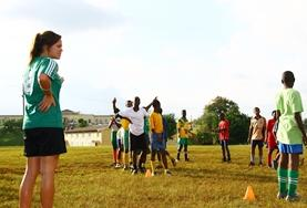 A volunteer sports coach teaches physical education to a group of children in Jamaica.