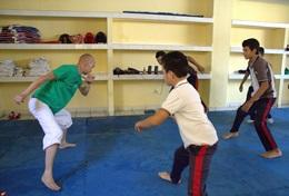 A volunteer teaches children capoeira during a physical education class in Mexico.