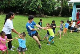 Volunteers play tug-of-war with children during a physical education class in Samoa.
