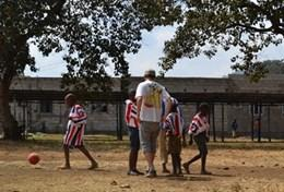A volunteer teaches a physical education class to young children in Tanzania.