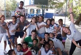 A group of teenagers and their volunteer coach at an after school sports program abroad.