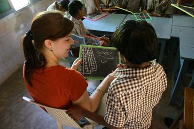 A Projects Abroad Teaching volunteer helps teach a young boy arithmetic at a school in Bangladesh
