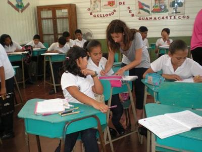Volunteer assisting students with classwork in a school in Costa Rica