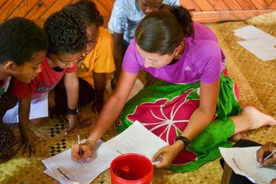 Children watch closely as Projects Abroad Care volunteer, Elizabeth from Austria, marks their quizzes.