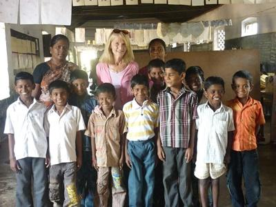 Volunteer poses with her classroom of students in a school in India on the Teaching project