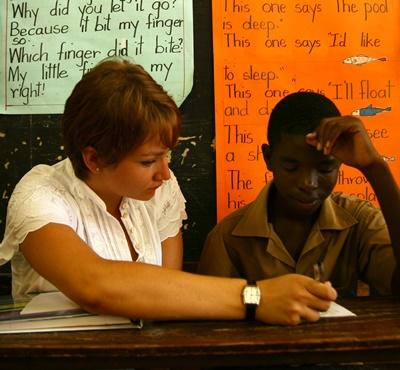 Volunteer tutors a students one-on-one in a classroom in Jamaica
