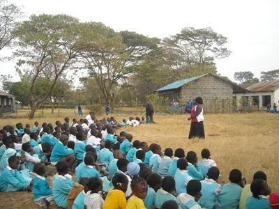 A female teacher teaches a class of elementary school children in Kenya, Africa