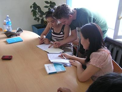 Teaching volunteer assists students with classwork in a school in Mongolia