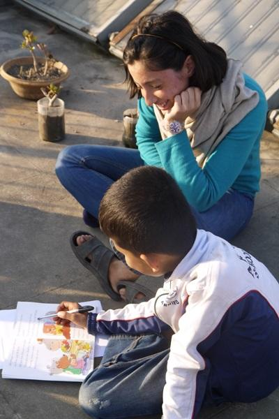 A Nepalese child has a reading lesson outdoors with a volunteer