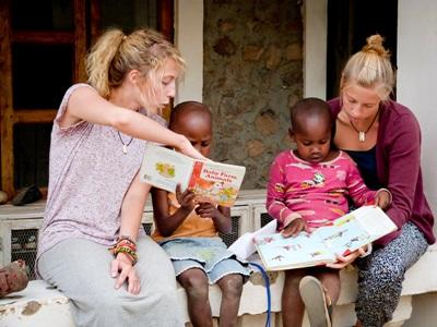 Tanzanian children read books with the help of volunteer teachers