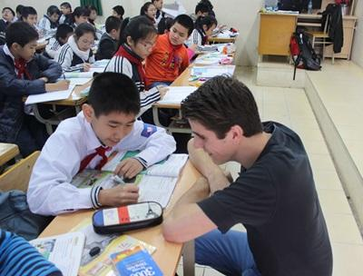 A Vietnamese school boy talks to a volunteer during class