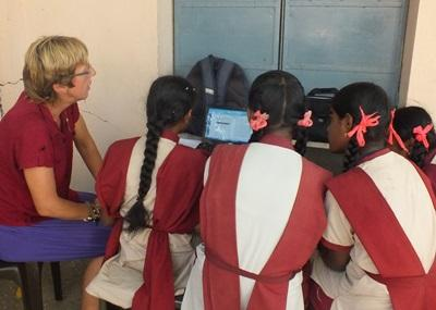 Volunteer teaching computer skills to young girls in India
