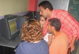 A volunteer explains how a computer program works to local teachers in Morocco.