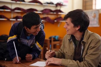 Projects Abroad Teaching volunteer assists a local student at a school in a developing country.