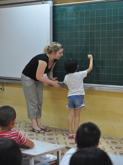 A Vietnamese students participates in class with the help of a Teaching volunteer