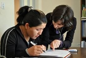 A university students practices English grammar with a volunteer in Bolivia.
