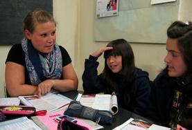 A volunteer helps teenagers in Argentina improve their French conversation.