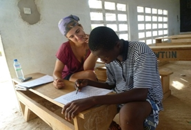 A volunteer teacher helps a student with his French conversation at a school in Togo.