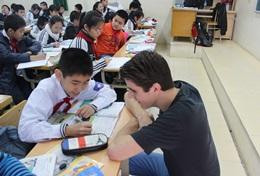 A volunteer helps a student with an exercise during a French class in Vietnam.