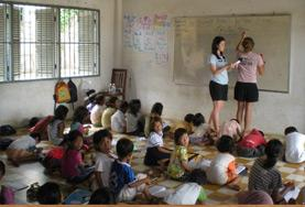Volunteers teach English to children at a school run by an NGO in Cambodia.
