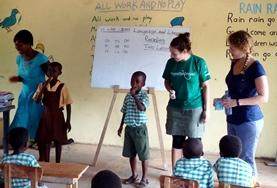 A volunteer helps a student complete an exercise during class in Ghana.