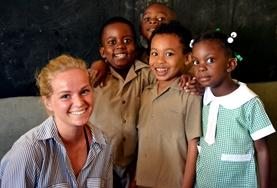A volunteer teaches English to a small group of children at a school in Jamaica.