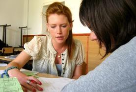 A volunteer helps a student with her English at a high school in Romania.