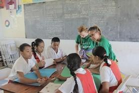 A group of students practice their English with volunteers at a school in Samoa.