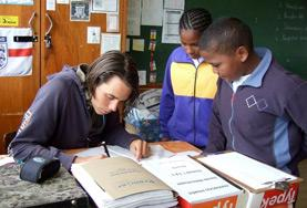 A volunteer helps two students with an activity during class in South Africa.