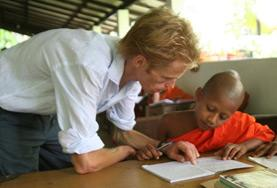 A volunteer teaches English to a young monk at a school in Sri Lanka.