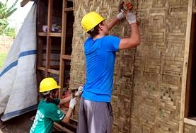 Volunteers work to build a new house in a rural area in Asia.