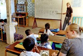 A volunteer teaching abroad leads an English class in a developing country.