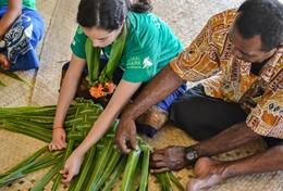 A volunteer learns how to weave baskets as part of her Culture & Community Project in the South Pacific