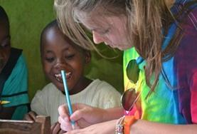 A volunteer helps a child complete an activity at a school in Ghana.
