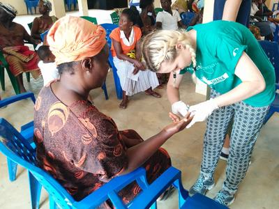 A Projects Abroad intern helps test blood sugar levels as part of a medical outreach in a rural part of Ghana, West Africa.