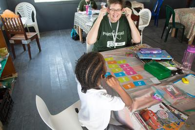 An older volunteer travelling with Projects Abroad in Belize helps a child improve her reading ability at a school.
